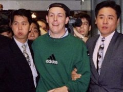 Nick Leeson is escorted by three Commercial Affairs Department (CAD) officers from a Singapore Airlines flight from Frankfurt which arrived in Singapore, in this November 23, 1995 file photo